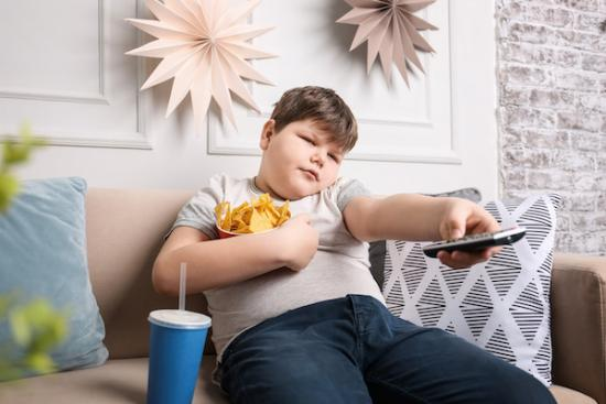Overweight child eating snacks and watching tv