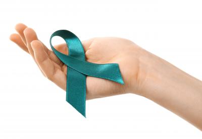 Hand holding a turquoise ribbon that represents awareness of Ovarian Cancer
