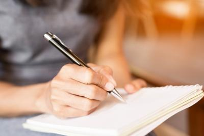 Woman writing down thoughts on paper