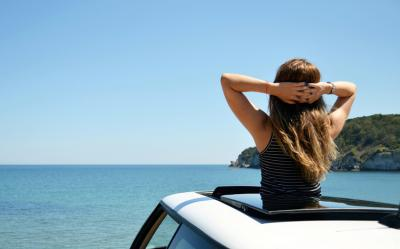 Woman looking at the ocean out of sun roof