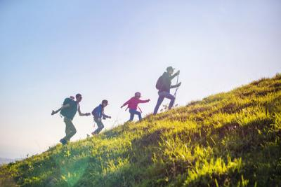 Family on a summer hike up a hill.