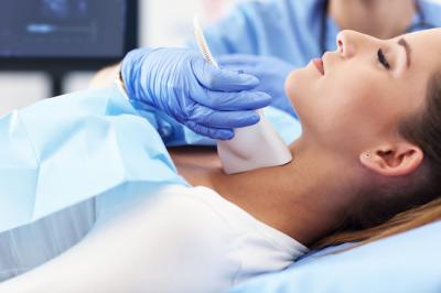 Woman getting her thyroid checked via ultrasound
