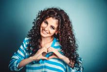 Smiling woman with long curly hair holding her hands in the shape of a heart over her chest.
