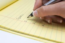 Female hand writing notes on a notepad