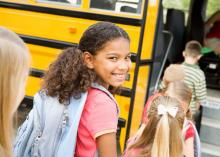 Young girl getting on a school bus