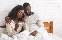 Man & Woman looking at a pregnancy test in bed