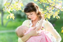 Woman breastfeeding her baby under a tree